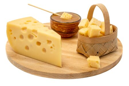 yellow Maasdam cheese, triangular piece cheese with holes, saucer with honey, basket of cheese wooden isolated white background