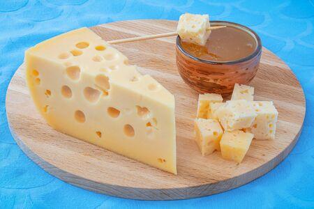 yellow Maasdam cheese, triangular piece cheese with holes blue napkin background Foto de archivo