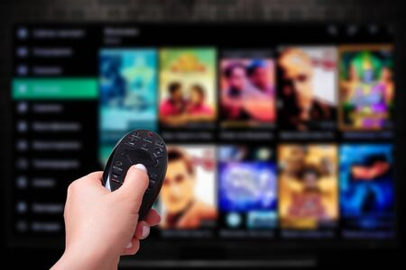 Multimedia streaming concept. Hand holding remote control. TV screen with lot of pictures. VoD content provider
