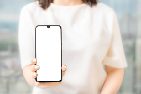 woman showing blank screen mobile phone while standing, Women hand show the mobile phone at the white screen, mockup