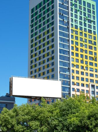Billboard on the background of a high-rise building. Empty or blank advertisement billboard to put your design on it.