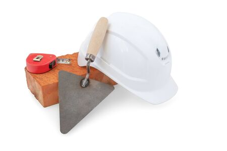 brick, construction helmet, tape measure and spatula isolated on a white background.