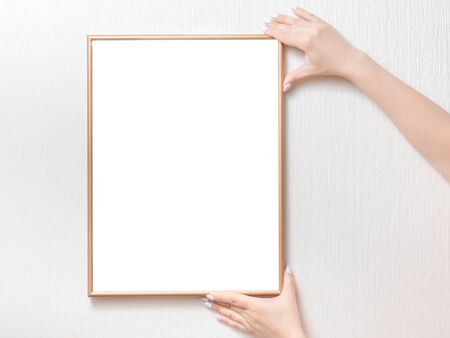 Woman hanging a frame mockup on a wall.