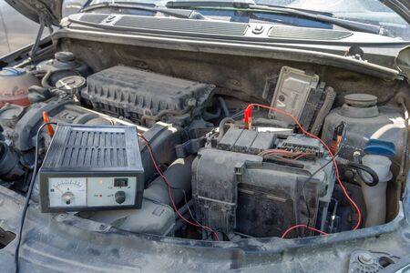 checking voltage of car battery under the open hood of the car. Automotive checkup concept. lifestyle Stockfoto