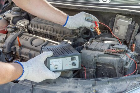 A closeup of a mechanics hands using jumper cables on a car battery. Automotive checkup concept