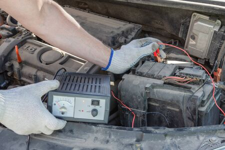 Close-up of male hands checking voltage of automobile battery under hood machine with accuracy. Automotive checkup concept. lifestyle.