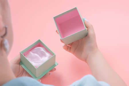 Young woman opens a empty jewelry gift, woman holding an open jewelery gift box. pink background. present concept.