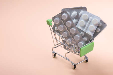 cart or shopping trolley full of various pharmaceutical pills or medicine. A grocery cart full of medical supplies pills and personal protective equipment against viruses. pharmacy shopping concept