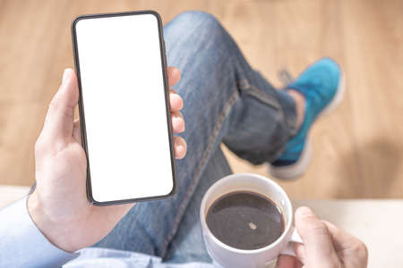 Cell phone mockup. Mockup image of hand holding black mobile phone with blank white screen on thigh with blue trainers shoes at vintage tile floor in cafe , feeling relax