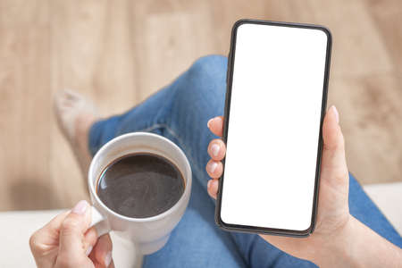 Mockup image of woman holding black mobile phone with blank white screen in cafe. Cropped shot view of woman's hands holding smart phone with blank copy space screen for your text message or information content, female reading text message on cell telephone