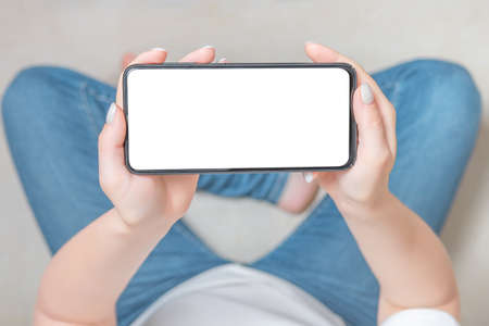 Mockup image blank white screen cell phone. female hands holding texting using mobile phone on sofa at home. Empty space for advertise text. Young woman in jeans looking at smartphone screen sitting on sofa at home. cell phone in horizontal position. People contact marketing business, technology