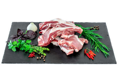 Raw pork ribs and condiments with fresh herbs laid out on a black stone cutting board. Whole raw pork ribs on dark black background. Raw pork ribs, pepper, basil, garlic and condiments
