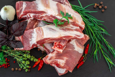 Raw pork ribs and condiments laid out on a black stone cutting board. Whole raw pork ribs with fresh herbs on dark black background. Raw pork ribs, pepper, basil, garlic and condiments. Close-up Archivio Fotografico