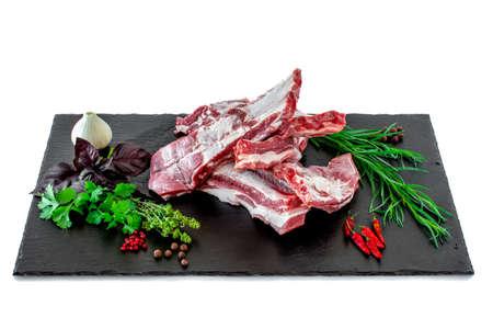 raw pork ribs with fresh herbs on a stone cutting board. Raw pork ribs with fresh herbs and condiments laid out on a black stone cutting board.