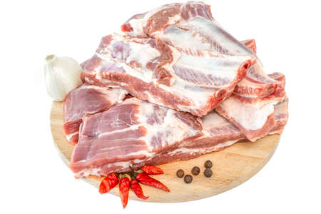 Raw pork ribs and condiments laid out on a wooden cutting board. Whole raw pork ribs with spice on wooden background. Raw pork ribs, pepper, garlic and condiments Isolated on white background