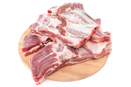 Raw pork ribs laid out on a wooden cutting board. Whole raw pork ribs with spice on wooden background. Close-up. Isolated on white.