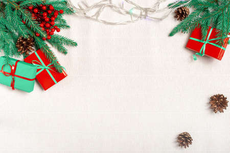 Christmas frame made of fir branches, red holly berries, Christmas gifts, Christmas wallpaper. Flat lay, top view, copy space.
