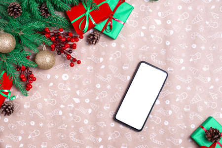mobile phone in Christmas decorations. mockup cell phone with blank screen in christmas time. Christmas corner with mobile phone