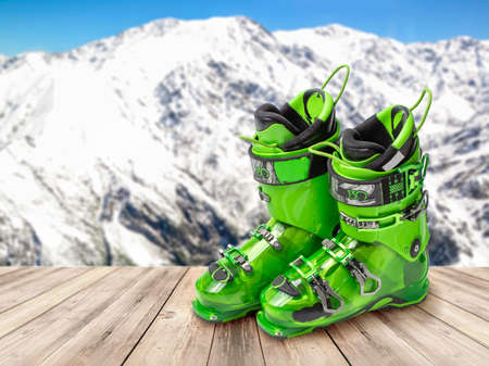 ski boots on a wooden table against the background of mountains. Professional ski boots, green sports ski boots