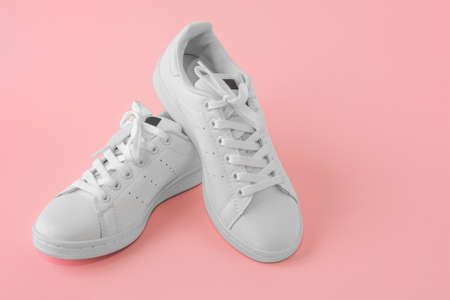 Pair of new white sneakers on pink background. New white leather sneakers sports shoes. sports shoes for running, tennis, jogging. Copyspace