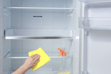 Hand cleaning refrigerator. fridge cleaning - spray bottle with detergents for washing the fridge. hand washing refrigerator inside with detergent Imagens