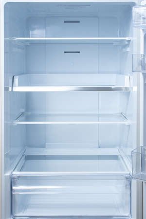 Empty open fridge with shelves, refrigerator. mockup background empty shelves for your products. open fridge shelf. Interior of an empty open white refrigerator. Vertical Stockfoto