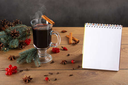 Opened notebook, fir branches, glass of mulled wine, spices and cones on wooden background. Writing plans for the new year. new start concept