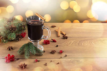 Cup of christmas mulled wine or gluhwein with spices and on rustic wooden table. Traditional drink on winter holiday. Christmas mulled wine and spices with space for text