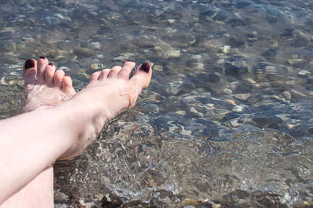 Women's feet on sea pebbles near the water on the shore.