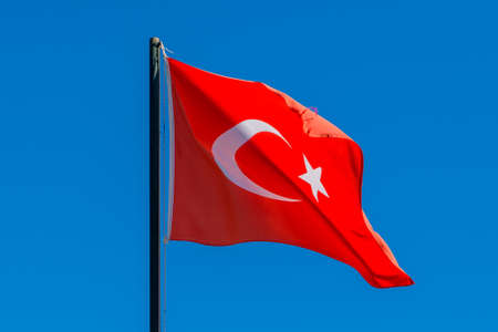Flag of Turkey rise waving to the wind with sky in the background. Waving national flag of Turkey. concept of tourism, economy and politics, close up.