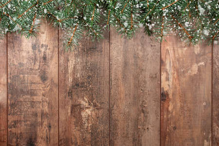 Christmas background. Old wood background with fir branches and snowflakes. Space for a greeting message. Christmas card. Top view. Effect of snowflakes.