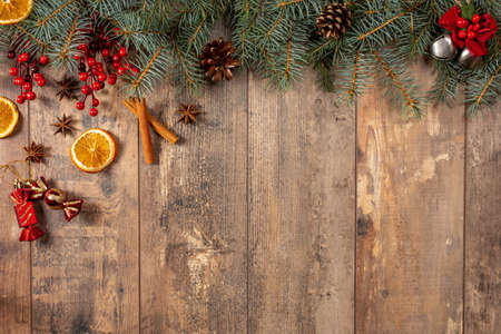 Christmas Evergreen Branches and Berries Over Rustic Wood Horizontal Background, Christmas branch corner border with berries and pine cones on a rustic old wood background 版權商用圖片