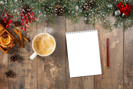 Cup of hot cocoa or chocolate, holiday decorations and notebook with to do list on wooden vintage table from above, christmas planning concept. Notebook on wooden table with New Year and Christmas