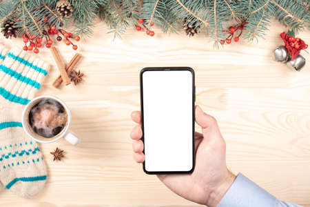 Modern cellphone with white blank screen in woman hands. Mobile phone mockup in woman hands. Christmas and new year decorations on blurry background. top view