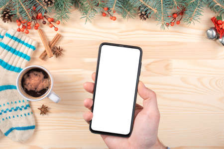 Christmas mockup phone. Mockup Smartphone on blurry Christmas Background With Christmas Ornaments On White wooden table. top view. flatlay
