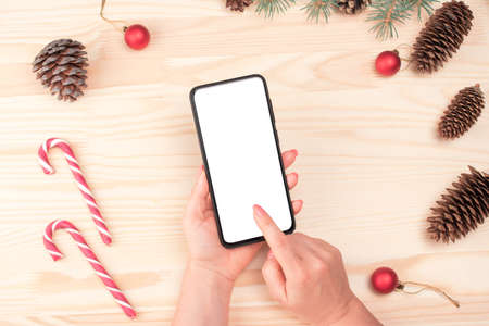 Christmas online shopping. Female buyer makes order at screen of smartphone with copy space. Woman buys presents for xmas eve. Winter holidays sales