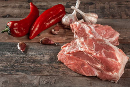 fresh meat with ingredients for cooking on dark background. pepper and garlic ingredients for cooking pork. pork fillet is ready for cooking Stok Fotoğraf