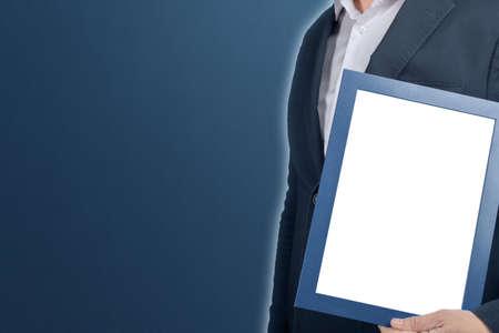 拿着在蓝色背景的大型模型商人文凭框架。拿着空的图片证明毕业框架的人。员工与空白的标志。copyspace.