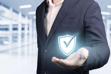 business information security concept. businessman holds security symbol in hand. concept of cyber security, data protection, protection against hacker attacks and viruses. blurred office background