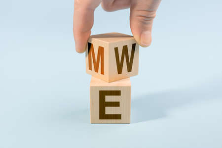 Hand flip wood cube with me or we on blue background. Teamwork concept. Hand turns dice and changes the word ME to WE. copy space