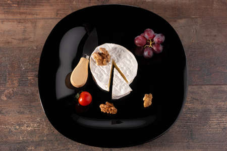 Delicious brie cheese on black plate. wooden rustic table. Brie type of cheese. Camembert. Fresh Brie cheese and a slice on stone board. Italian, French cheese.