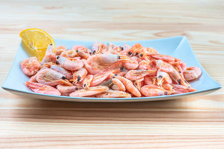 fresh seafood shrimp in white plate. fresh shrimps served on plate. boiled shrimp unpeeled prawns cooked in the seafood restaurant