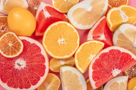 Pile of fresh citrus fruits. Top view of citrus fruits, Orange, tangerine, lemon, lime and grapefruit slices or circles on pink background. top view
