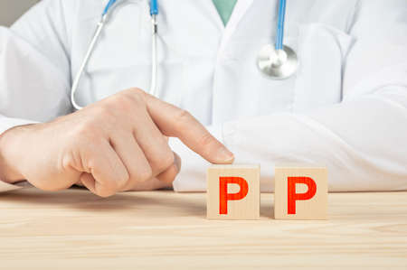 essential vitamins and minerals for humans. doctor recommends taking vitamin PP. doctor talks about the benefits of vitamin PP. PP Vitamin - Health Concept. PP alphabet on wood cube.