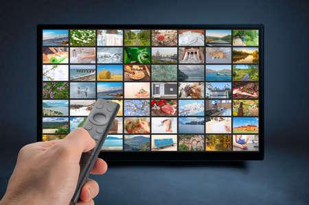 Male hand holding TV remote control. Multimedia streaming concept. VoD content provider concept. Television streaming video concept. Video service with internet streaming multimedia shows, series. Фото со стока