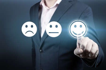 Businessman giving rating with happy icon. Businessman pressing happy icon, Customer service evaluation concept. Customer satisfaction survey concept