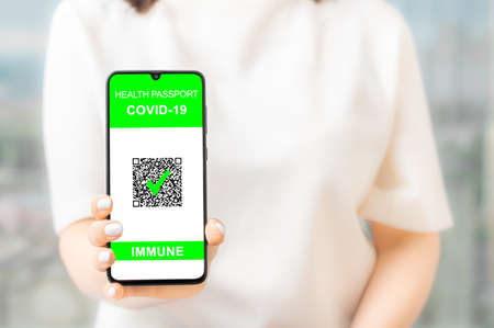Woman hand hold and show phone with health passport covid-19. Mobile phone with immune digital health passport for covid-19 held by an unrecognizable woman