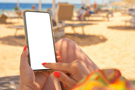Closeup of young woman's hands using white mobile smartphone Mockup on the beach, beach resort and Sea in the background. woman holding mobile phone with blank desktop screen while sitting on beach