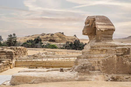 Full profile of Great Sphinx including pyramids of Khafre in the background on a cloudy sky day in Giza, Cairo, Egypt. no people. ancient Egyptian civilization. Great sphinx