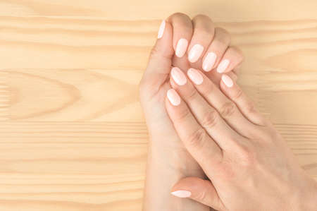 Closeup shot of a woman in a nail salon getting a manicur. women's hands with an excellent manicure on the background of a wooden table. light pink nails. top view